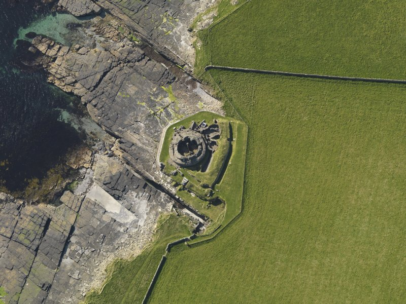 Oblique aerial view centred on Midhowe broch, Rousay, taken from the SE.