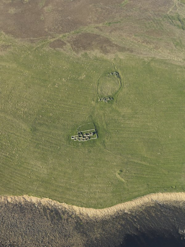 Oblique aerial view centred on the remains of Eynhallow monastery, taken from the SW.
