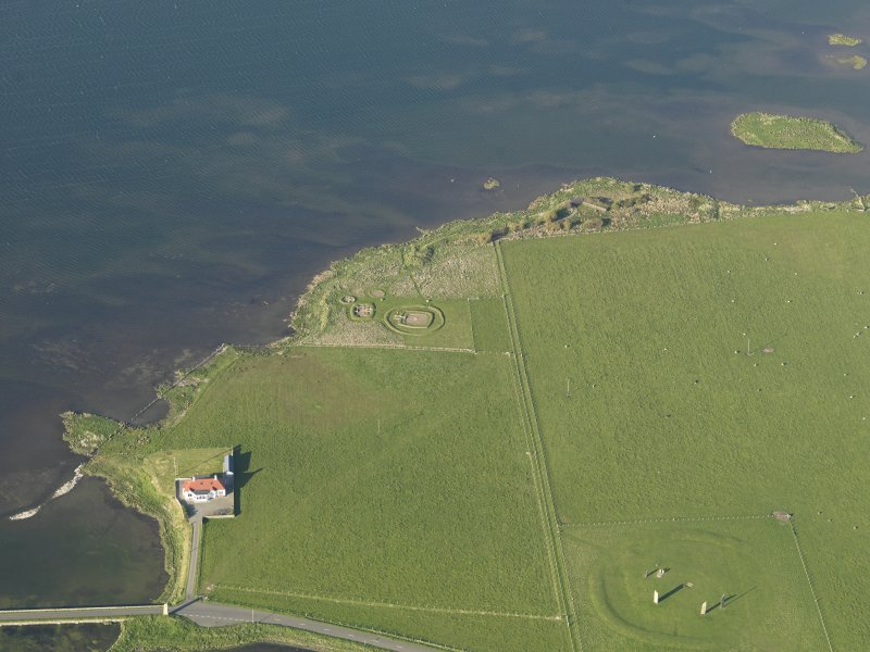 Oblique aerial view of the Stones of Stenness an the Barnhouse settlement, taken from the SW.