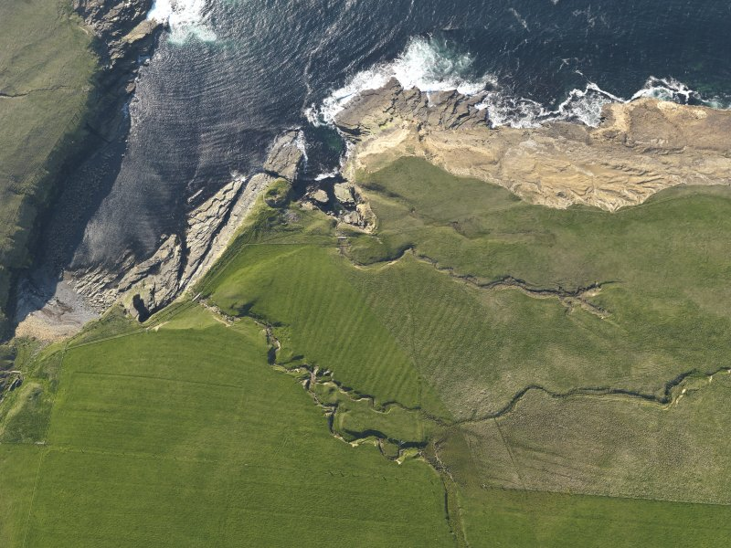 Oblique aerial view centred on the Broch of Borwick and the remains of the rig and furrow, taken from the SW.