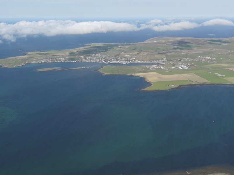 General oblique aerial view looking towards Bu Point with Stromness beyond, taken from the NE.