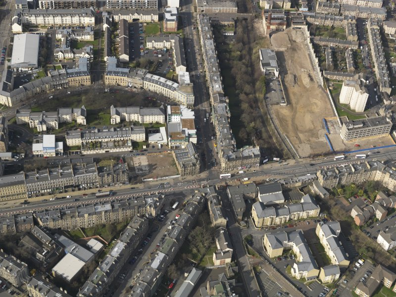 Oblique aerial view centred on Leith Walk with the site of the former tram and bus depot adjacent, taken from the SE.