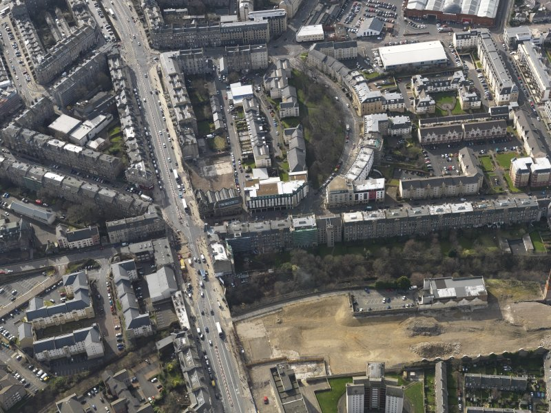 Oblique aerial view centred on part of  Leith Walk with the site of the tram and bus depot adjacent, taken from the NE.