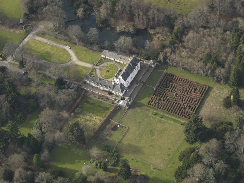 Oblique aerial view centred on the tower/country house with the garden adjacent, taken from the E.