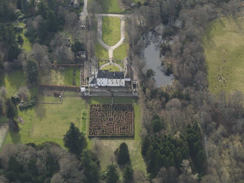 Oblique aerial view centred on the tower/country house with the garden adjacent, taken from the NE.