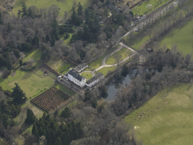 Oblique aerial view centred on the tower/country house with the garden adjacent, taken from the N.