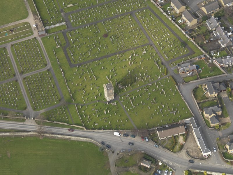 Oblique aerial view centred on the remains of the church with the graveyard adjacent, taken from the S.