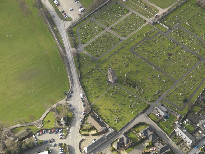 Oblique aerial view centred on the remains of the church with the graveyard adjacent, taken from the  ESE.