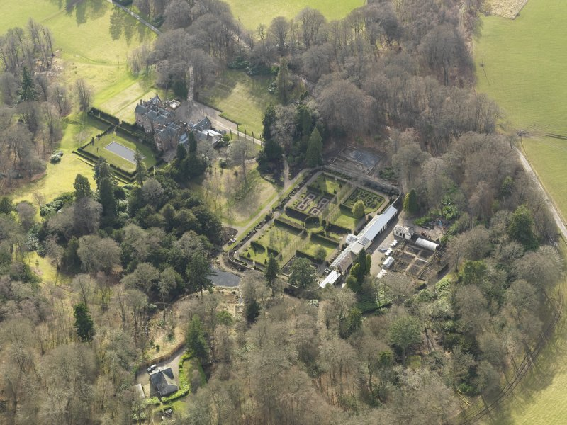 Oblique aerial view centred on the country house with the walled garden adjacent, taken from the NE.