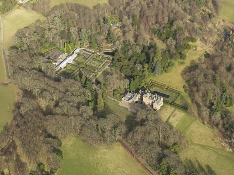 Oblique aerial view centred on the country house with the walled garden adjacent, taken from the SW.