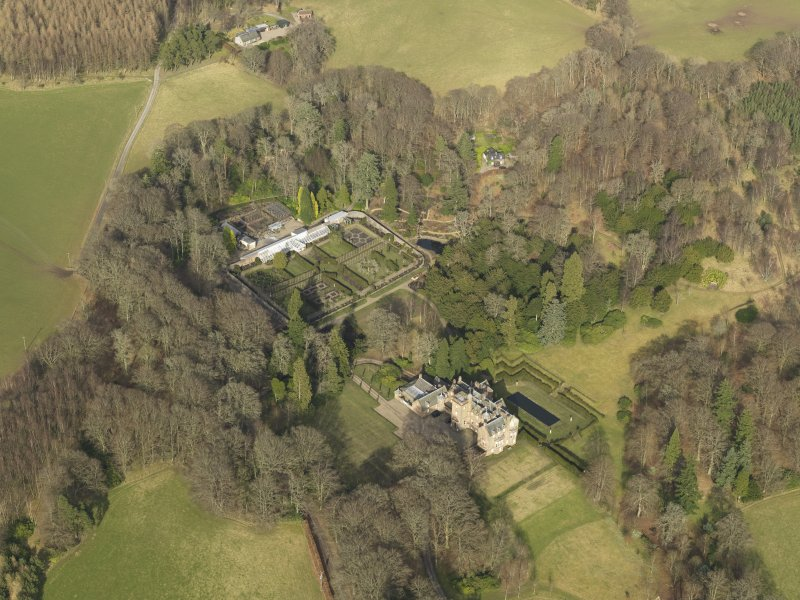 Oblique aerial view centred on the country house with the walled garden adjacent, taken from the SSW.
