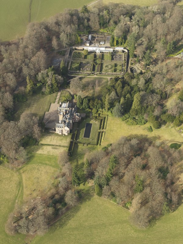 Oblique aerial view centred on the country house with the walled garden adjacent, taken from the S.
