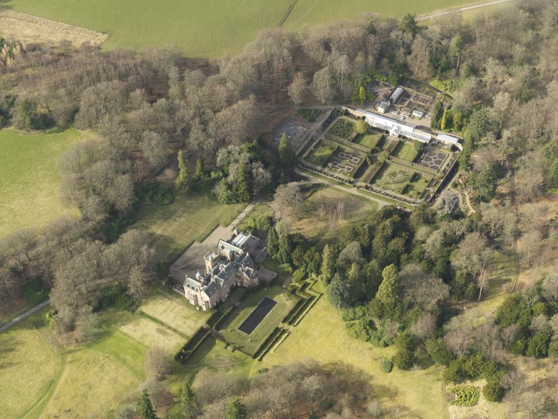 Oblique aerial view centred on the country house with the walled garden adjacent, taken from the SE.