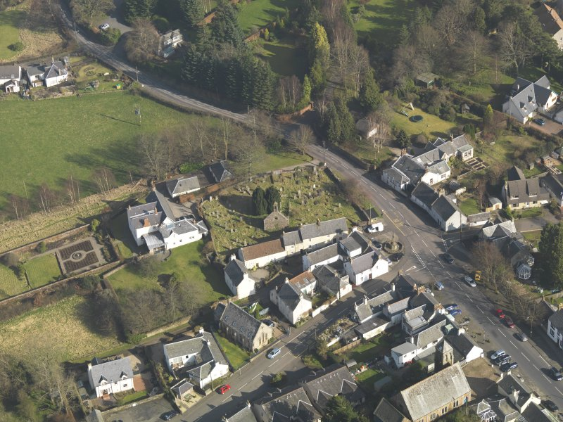 Oblique aerial view centred on the old parish church with the graveyard adjacent, taken from the SW.