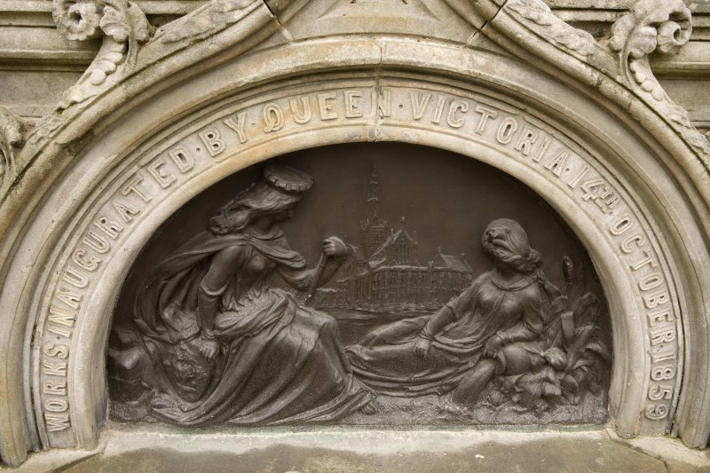Detail of bronze plaque with ogee-arched stone surround on ESE face of Stewart Memorial Fountain, Kelvingrove Park, Glasgow