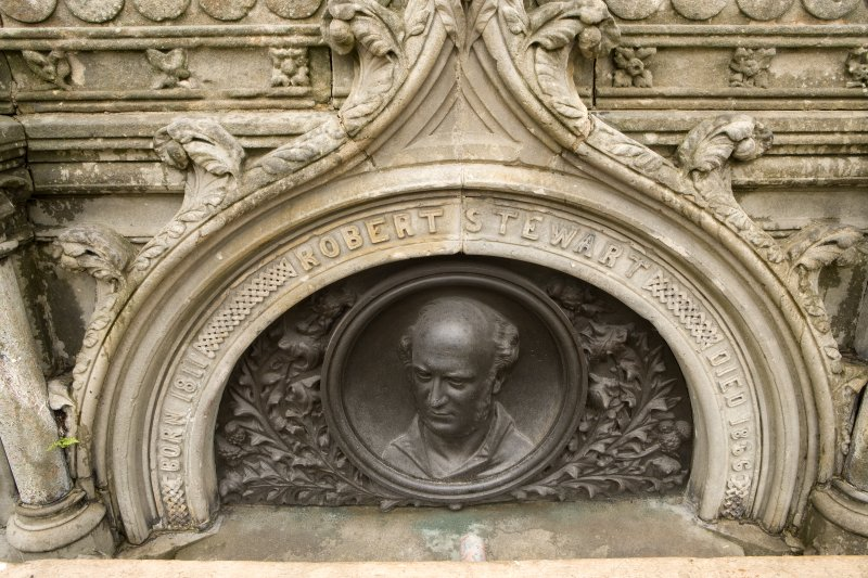 Detail of bronze commemorative plaque with ogee-arched stone surround on SSW face of Stewart Memorial Fountain, Kelvingrove Park, Glasgow