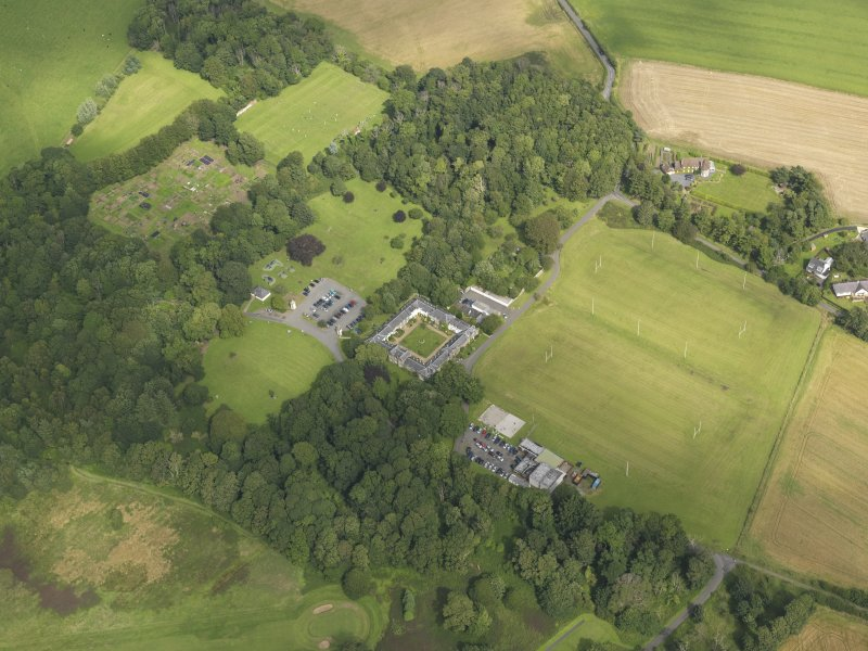 General oblique aerial view centred on the house and stables, taken from the SW.