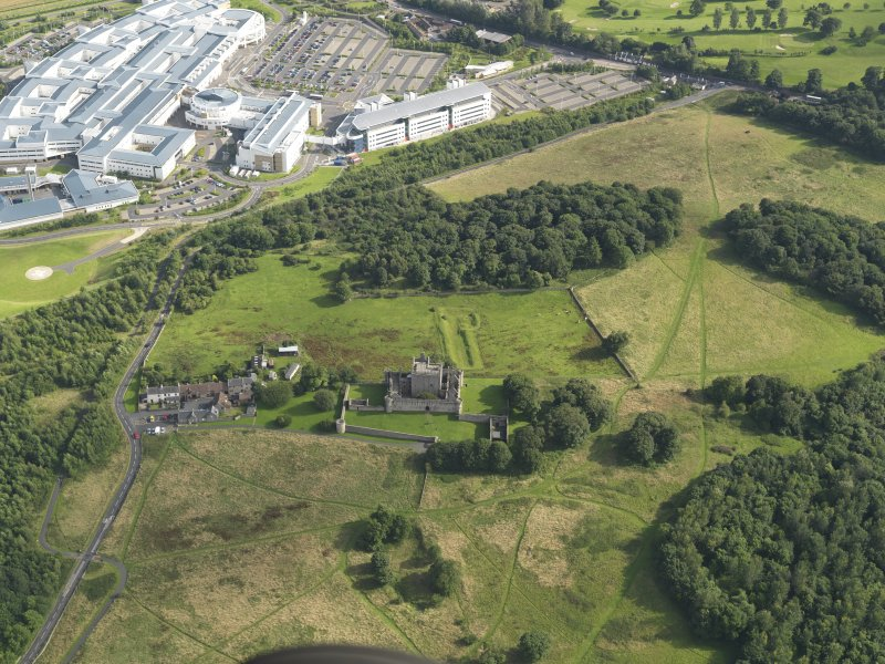 Oblique aerial view of Craigmillar Castle with the Royal Infirmary of Edinburgh, Little France, beyond, taken from the NNW.