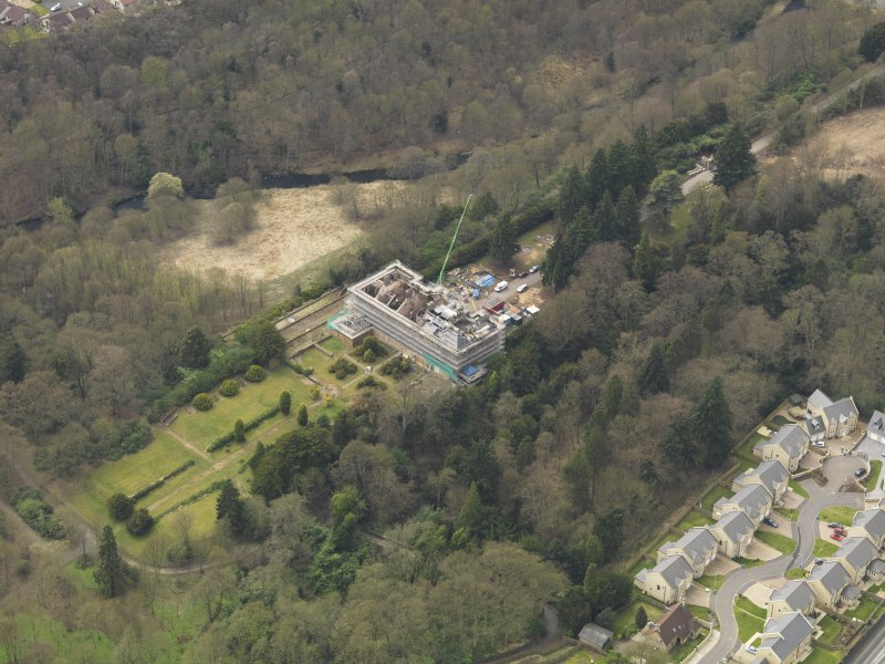General oblique aerial view centred on the fire damaged house, taken from the NE.