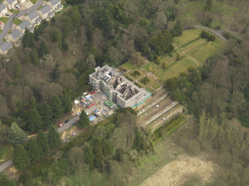 Oblique aerial view centred on the fire damaged house, taken from the SW.