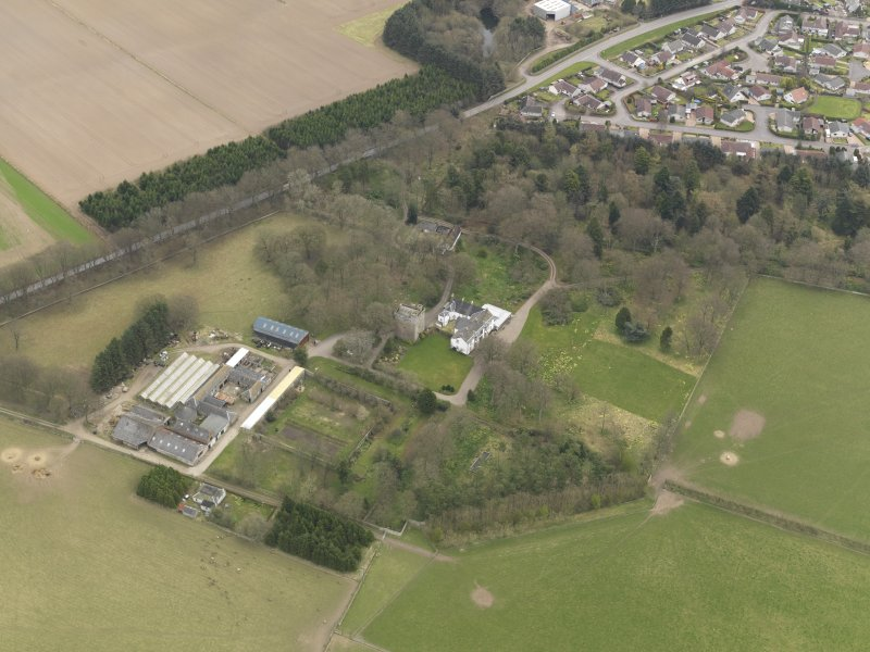 Oblique aerial view centred on the country house with the tower-house adjacent, taken from the SW.