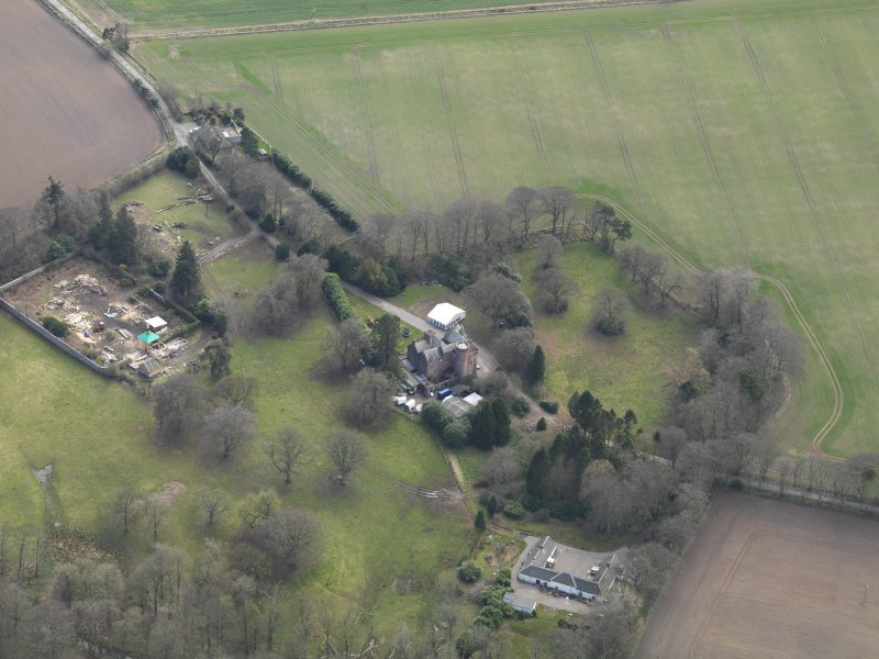 Oblique aerial view centred on the country house with the walled garden and stables adjacent, taken from the NNW.