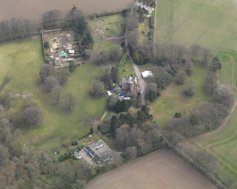 Oblique aerial view centred on the country house with the walled garden and stables adjacent, taken from the NW.