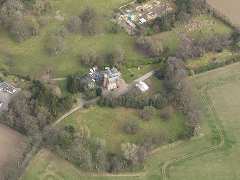 Oblique aerial view centred on the country house with the walled garden and stables adjacent, taken from the SW.