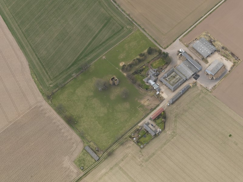 General oblique aerial view centred on the remains of the tower-house with the farmstead adjacent, taken from the SE.