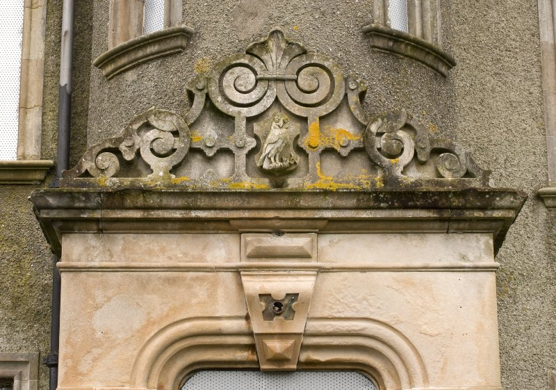 Detail of ornate carved main entrance door pediment with 'owl' motif and nailhead decoration.