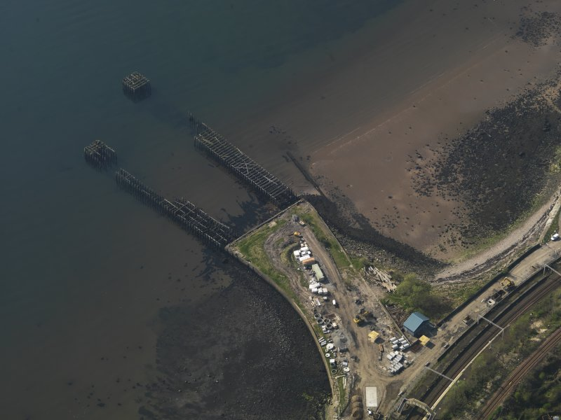 Oblique aerial view centred on the remains of the pier, taken from the E.