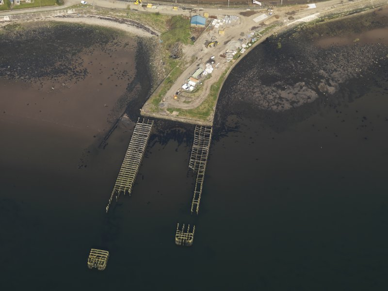 Oblique aerial view centred on the remains of the pier, taken from the WSW.