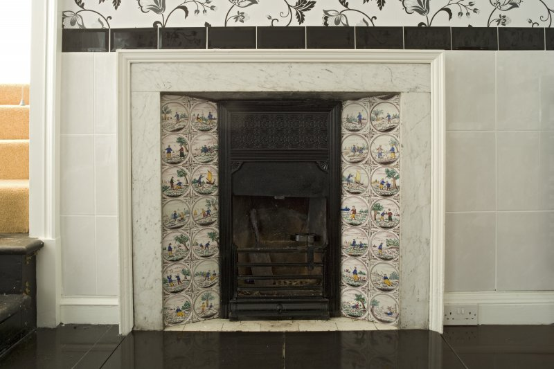 Interior. 1st floor, bathroom, detail of tiled fireplace
