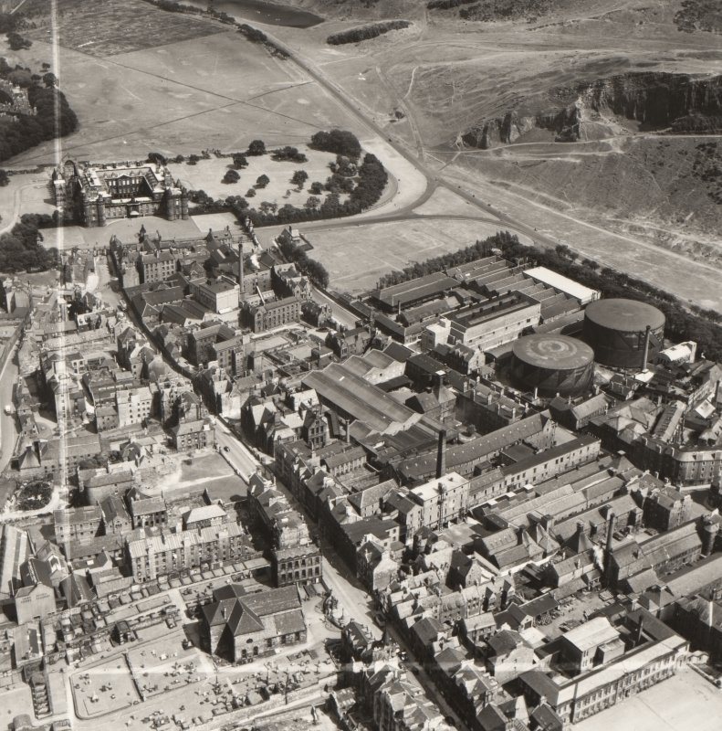 Oblique aerial view of the Canongate area, Edinburgh, c1951 including Holyrood Palace, the Meadow Flat Gas Holders (now the site of Dynamic Earth) and Holyrood Brewery (now the site of the Scottish Parliament).