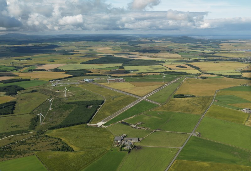 General oblique aerial view centred on the remains of the airfield with the windfarm adjacent, taken from the E.