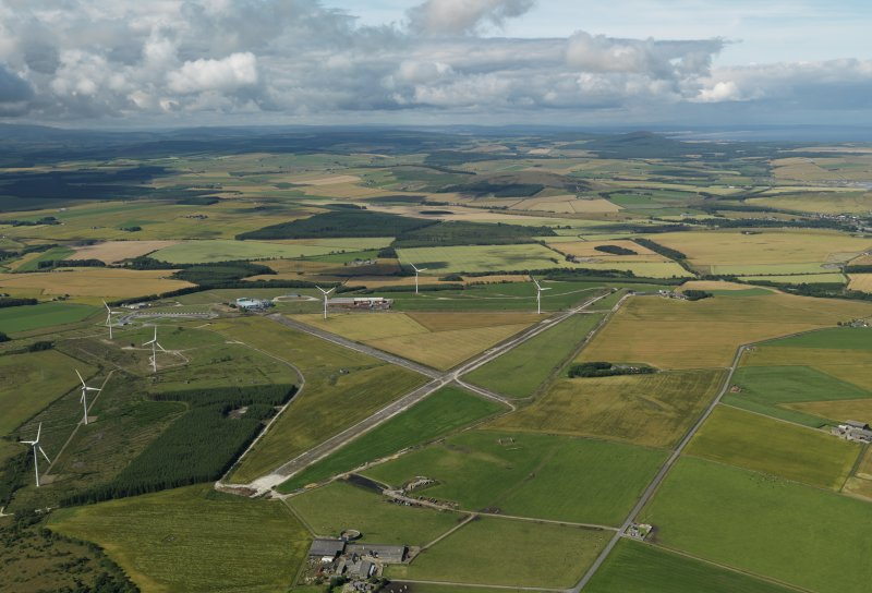 General oblique aerial view centred on the remains of the airfield with the windfarm adjacent, taken from the ENE.