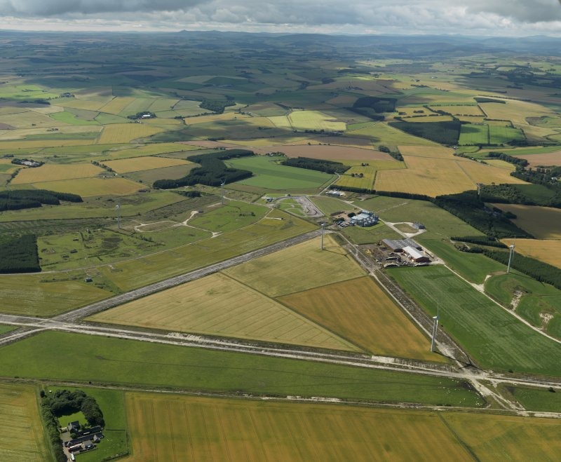 General oblique aerial view centred on the remains of the airfield with the windfarm adjacent, taken from the N.