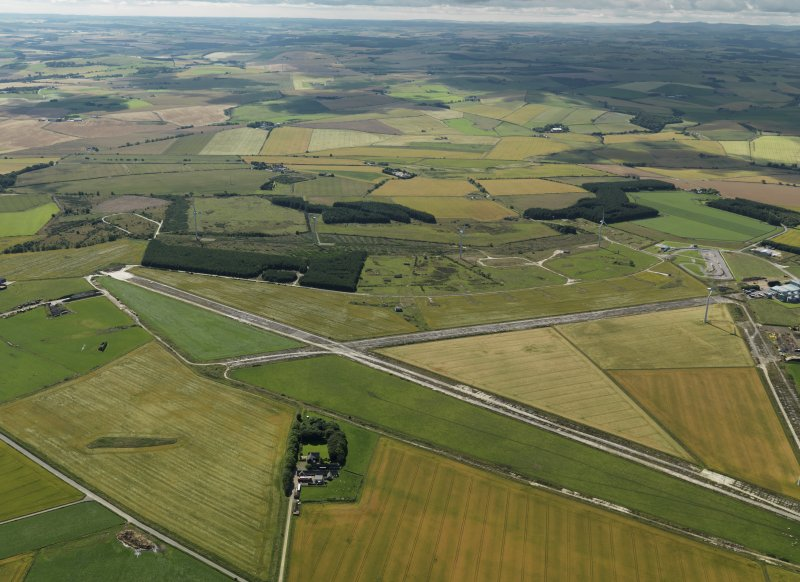 General oblique aerial view centred on the remains of the airfield with the windfarm adjacent, taken from the NNW.