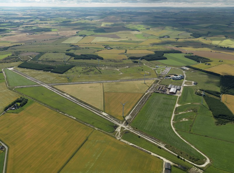 General oblique aerial view centred on the remains of the airfield with the windfarm adjacent, taken from the NW.