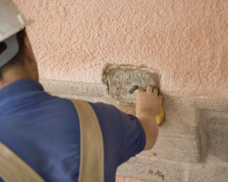 Mason preparing wall to take new false spout
