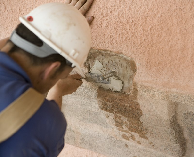 Mason applying mortar to castle prior to fitting new false spout
