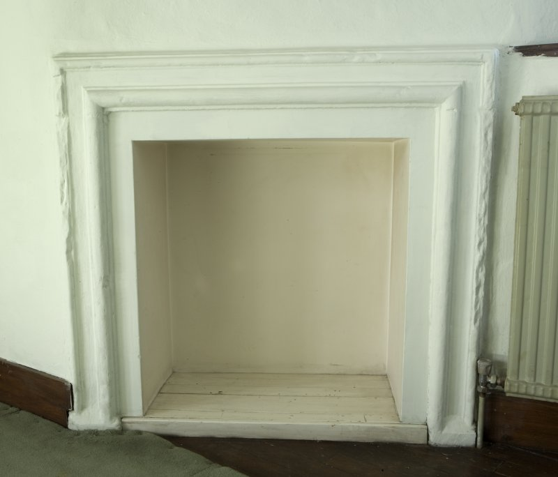Interior. Upper floor plaster ceiling room, detail of N wall fireplace
