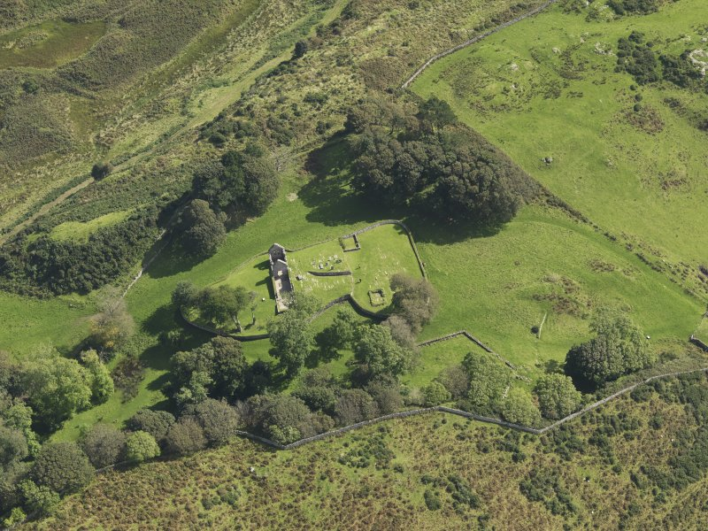 Oblique aerial view centred on the ruins of the church and the burial ground, taken from the W.