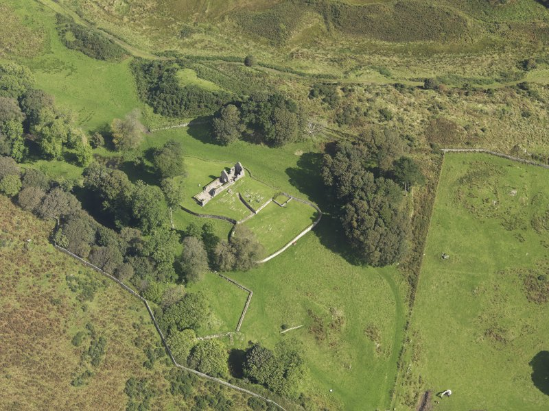 Oblique aerial view centred on the ruins of the church and the burial ground, taken from the SW.