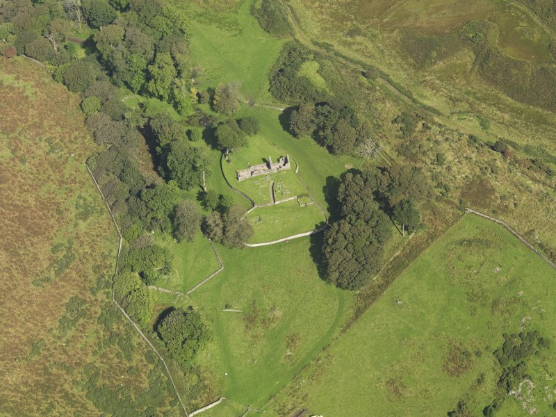 Oblique aerial view centred on the ruins of the church and the burial ground, taken from the S.