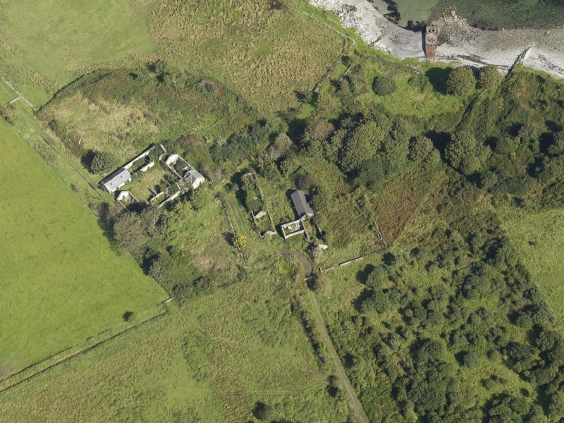 Oblique aerial view centred on the two farmsteads and site of the chapel (at the top left), taken from the SSW.