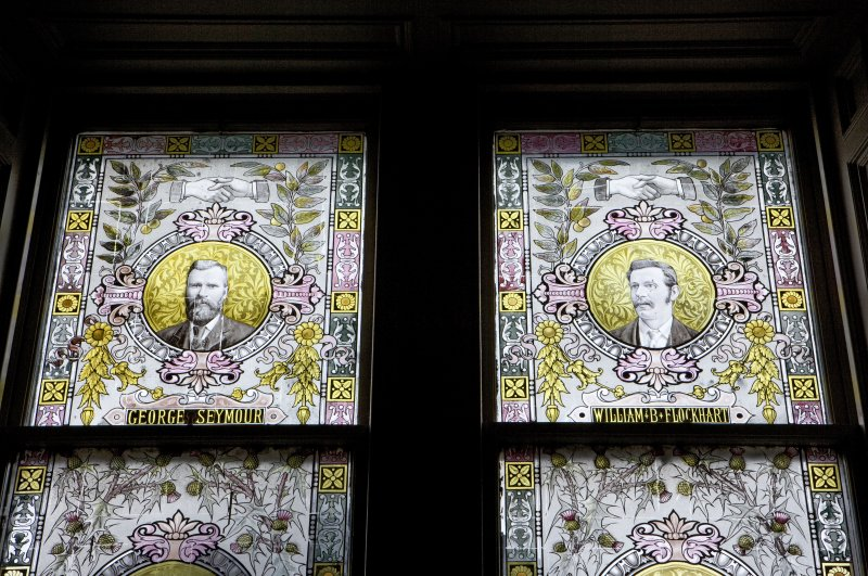 Interior. W staircase, stained glass window, detail of benefactors, George Seymour and William B. Flockart