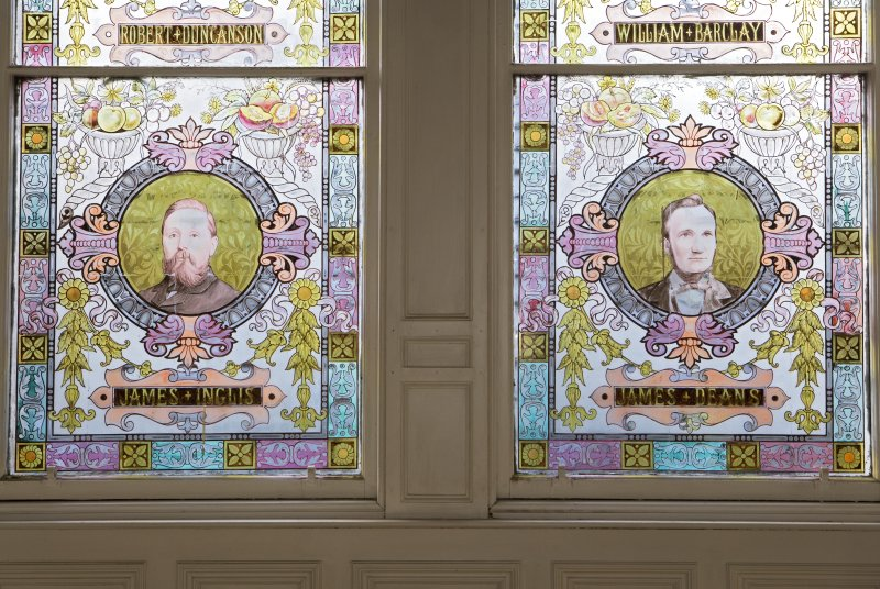 Interior. W staircase, stained glass window, detail of benefactors, James Inglis and James Deans