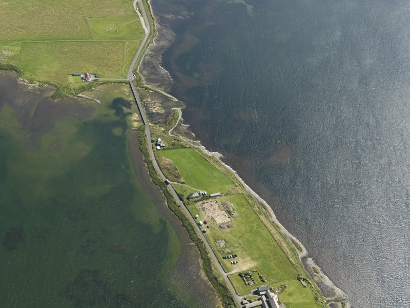 Oblique aerial view centred on the excavations of Brodgar settlement, taken from the NW.