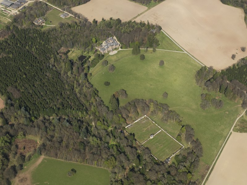 Oblique aerial view of the country house with the walled garden adjacent, taken from the SW.